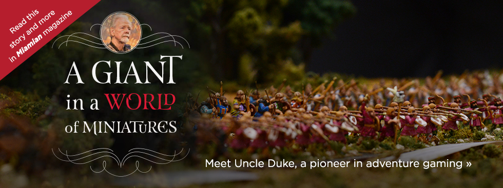 A giant in a world of miniatures. Meet Uncle Duke, a pioneer in adventure gaming » Read this story and more in Miamian magazine. Photo of intricately painted warrior miniatures lined up in a grassy playing field.
